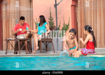Kids playing in swimming pool - Stock Photo