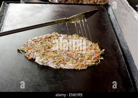 Uttapam being prepared on tawa - Stock Photo