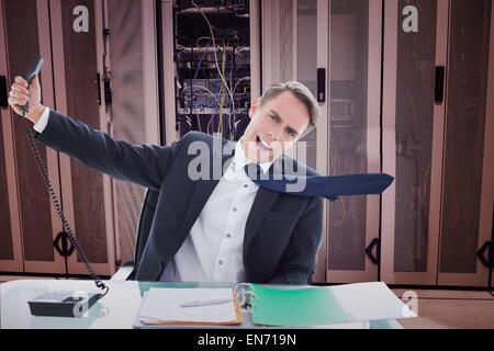 Composite image of businessman shouting as he holds out phone - Stock Photo