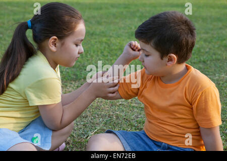 Girl putting band-aid on brothers arm - Stock Photo