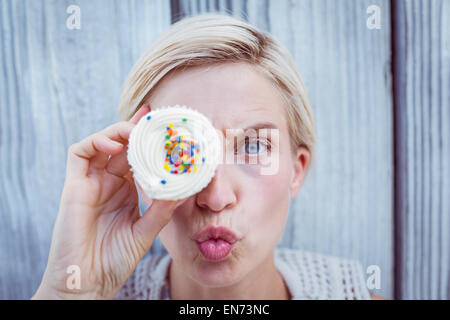 Pretty blonde woman grimacing with cupcake - Stock Photo
