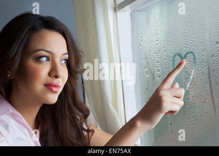 Woman drawing heart on window - Stock Photo