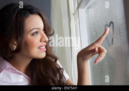 Woman drawing heart on window - Stock Photo