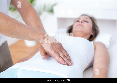 Physiotherapist examining his patients stomach - Stock Photo