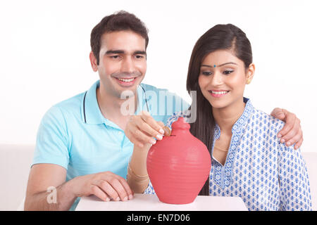 Couple putting money in piggy bank - Stock Photo