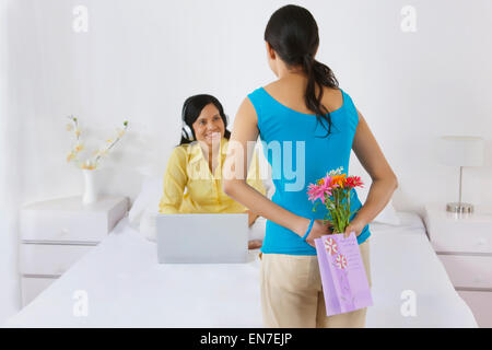 Girl surprising her mother on mothers day - Stock Photo