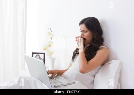 Woman yawning while working on laptop - Stock Photo