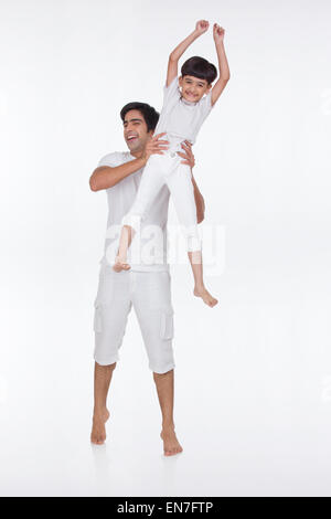 Portrait of father lifting son in the air - Stock Photo