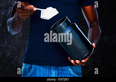 Composite image of mid section of man holding a scoop of protein mix - Stock Photo