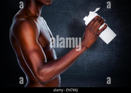 Composite image of mid section of a sporty young man holding protein drink - Stock Photo