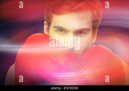 Composite image of fit man wearing red boxing gloves - Stock Photo