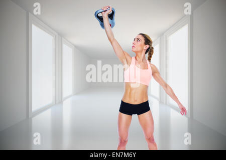 Composite image of female crossfitter lifting up kettlebell - Stock Photo