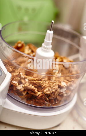 Kernel walnuts in a food processor ready to be crushed for prepare dessert - Stock Photo