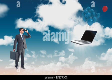Composite image of businessman looking through binoculars - Stock Photo