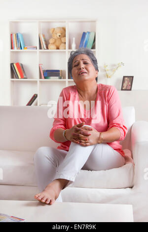 Old woman holding knee in pain - Stock Photo