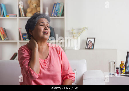Old woman with pain in neck - Stock Photo