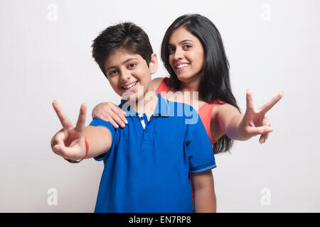 Portrait of brother and sister showing victory sign - Stock Photo
