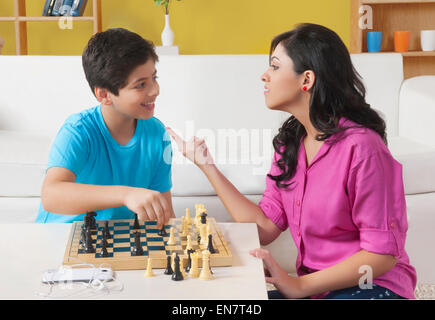 Sister and brother playing chess in living room - Stock Photo