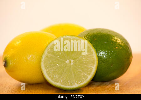 Lemons and Limes Isolated on wooden surface - Stock Photo