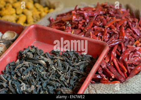 Sacks of dried chillies and dried mango for sale at the market - Stock Photo