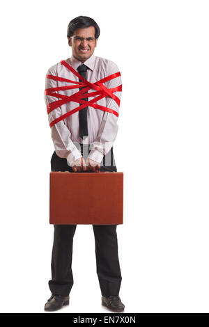 Businessman tied up with red ribbon - Stock Photo