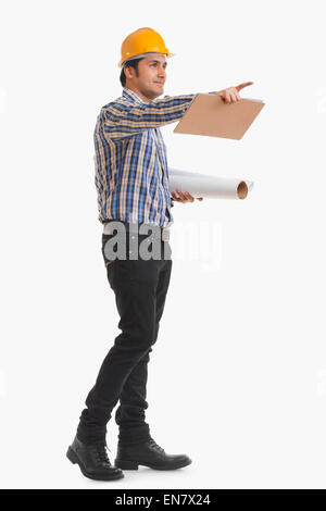Portrait of smiling contractor holding blueprint and clipboard pointing - Stock Photo