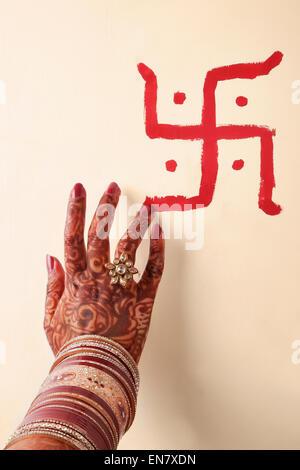 Close-up of a Brides hand making swastika on wall - Stock Photo