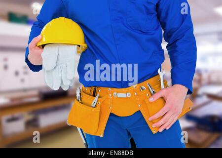 Composite image of handyman holding helmet - Stock Photo