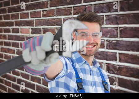 Composite image of handyman wearing protective glasses while holding wrench - Stock Photo