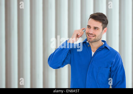 Composite image of happy young male mechanic using mobile phone - Stock Photo