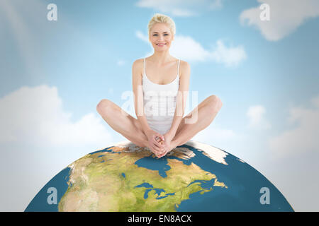 Composite image of toned young woman doing the butterfly stretch - Stock Photo