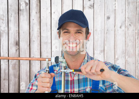 Composite image of portrait of happy plumber fixing pipe - Stock Photo