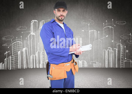 Composite image of handyman in blue overall writing on clipboard - Stock Photo