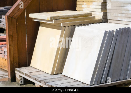New paving slabs stacked on a pallet ready for sale, UK. - Stock Photo