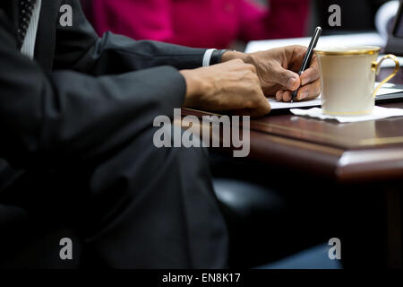 President Barack Obama takes notes during a video conference with President Ashraf Ghani of Afghanistan in the Situation - Stock Photo