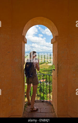 Vertical portrait of a tourist taking photographs from the Iznaga Tower at Valle de los Ingenios. - Stock Photo