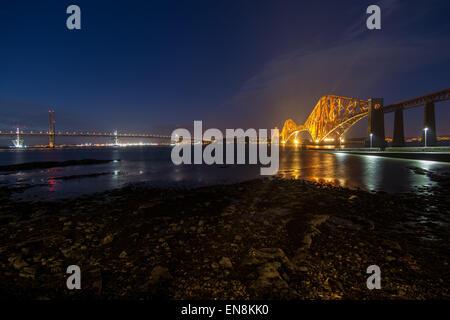 Forth Rail and road Bridges illuminated at night, South Queensferry, Edinburgh, Midlothian, Scotland, United Kingdom - Stock Photo