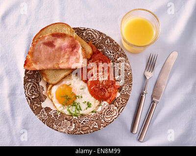 Breakfast, fried egg, tomatoes and bread with a ham - Stock Photo
