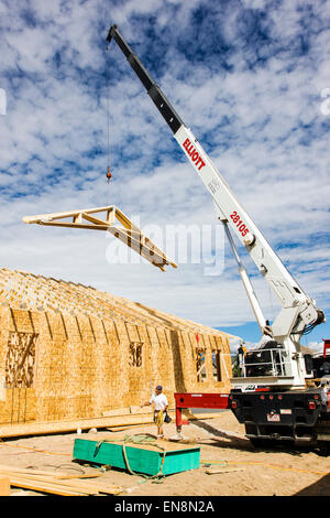 Construction of a Craftsman Style residential home in Colorado, USA. A crane lifts roof trusses into place. - Stock Photo