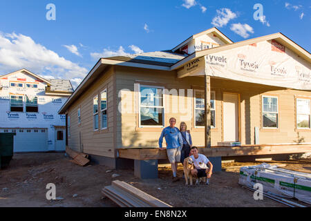 Family standing proudly in front of their new home under construction - Stock Photo