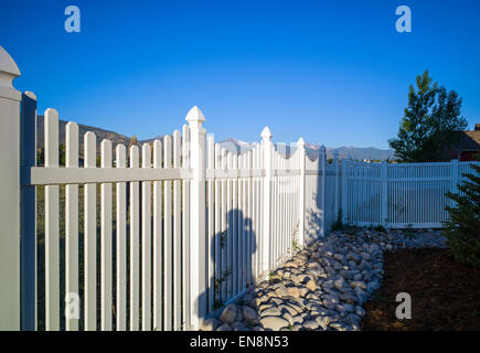 White vinyl picket garden fence in the yard of a Craftsman Style residential home in Colorado, USA - Stock Photo