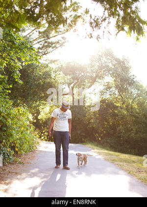 A young tan colored pit bull walks off leash with his owner on a sunny path in the park. - Stock Photo