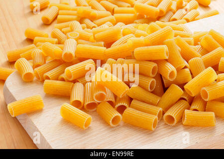 a pile of uncooked penne pasta on a kitchen wooden table - Stock Photo