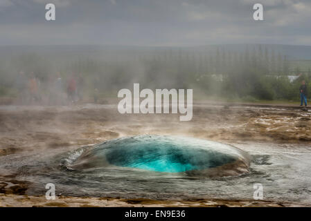 Strokkur Geyser just before it erupts, Iceland. Strokkur is a fountain geyser in the geothermal area beside the - Stock Photo