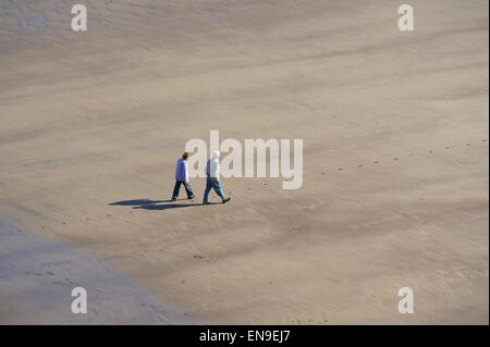 Elderly couple walking on beach in England UK - Stock Photo