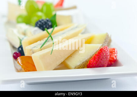 cheese with berries on a white plate - Stock Photo