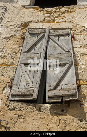 Old wooden shutters cover the window in the wall of a derelict house in the Dordogne France - Stock Photo