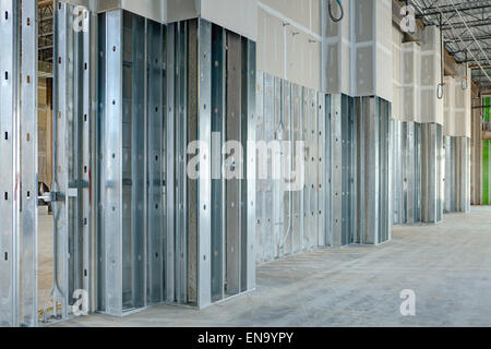 Steel studs used to frame in a large commercial building, with drywall covering. - Stock Photo