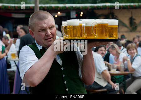waiter serving beer at the traditional Kirtag (fair) in Altaussee, Styria, Austria - Stock Photo