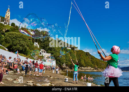 Two women creating some huge and amazing bubbles to entertain the crowd at festival No.6, 2014 in Portmeirion, Wales. - Stock Photo
